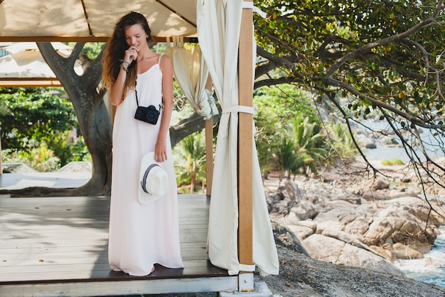 Young natural beautiful woman in pale gown posing in marquee, tropical vacation,