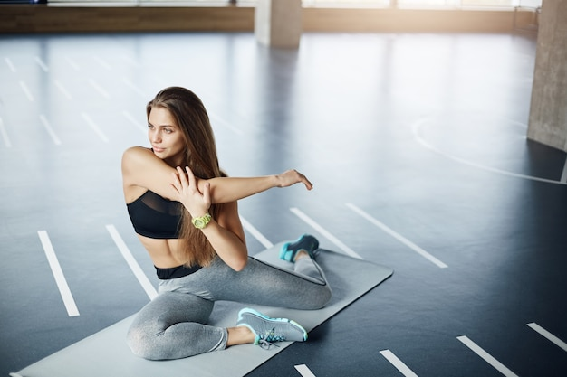 Young natural blonde adult woman stretching arms in gym working on her perfect body.