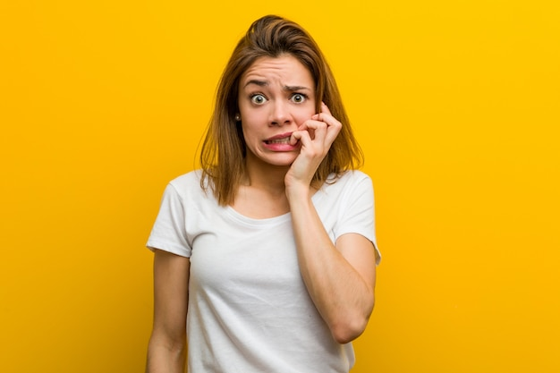 Young natural caucasian woman biting fingernails, nervous and very anxious.