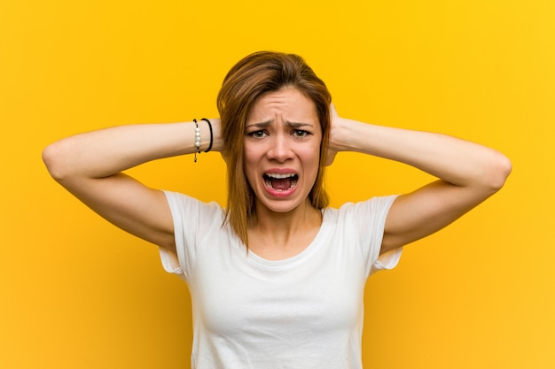 Young natural caucasian woman covering her ears with hands trying not to hear too loud sound.