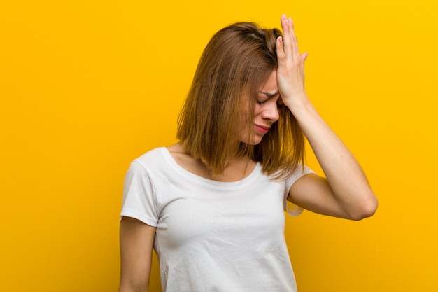 Young natural caucasian woman forgetting something, slapping forehead with palm and closing eyes.
