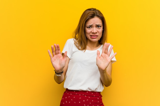 Young natural caucasian woman rejecting someone showing a gesture of disgust.