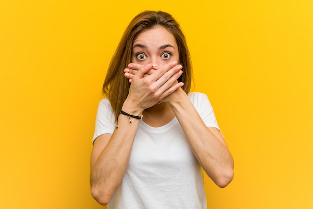 Young natural caucasian woman shocked covering mouth with hands.