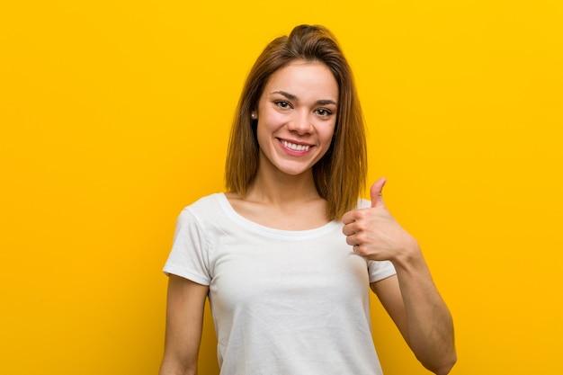 若い自然な白人女性の笑顔と親指を上げる