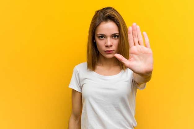 Young natural caucasian woman standing with outstretched hand showing stop sign, preventing you.