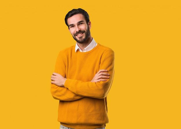 Молодой натуральный человек скрещивает руки, улыбается и расслаблен