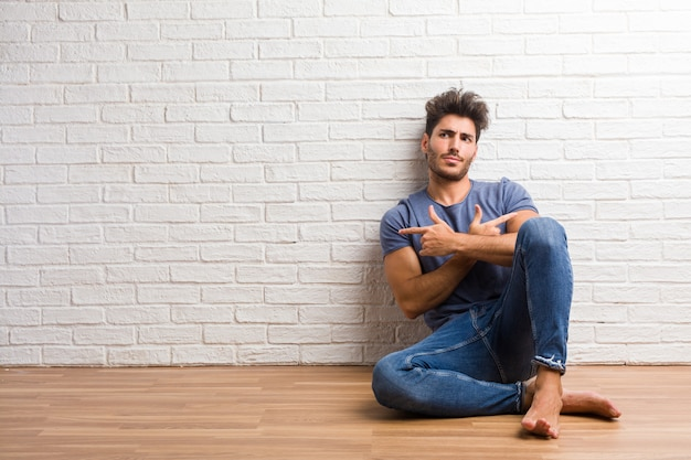 Young natural man sit on a wooden floor confused and doubtful, decide between two options