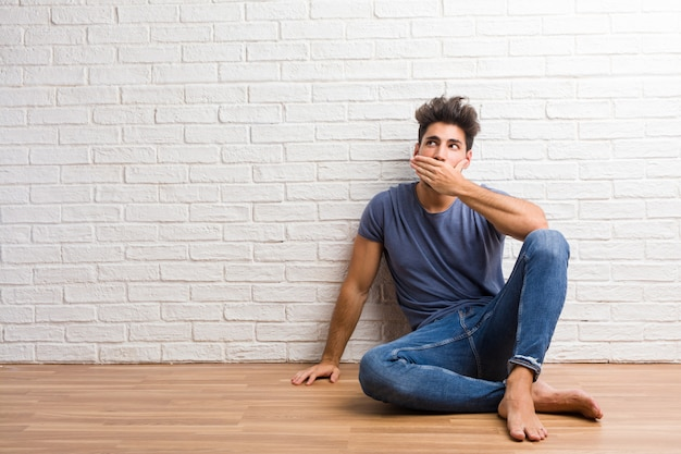 Young natural man sit on a wooden floor covering mouth, symbol of silence and repression, trying not to say anything