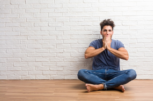 Young natural man sit on a wooden floor covering mouth, symbol of silence and repression