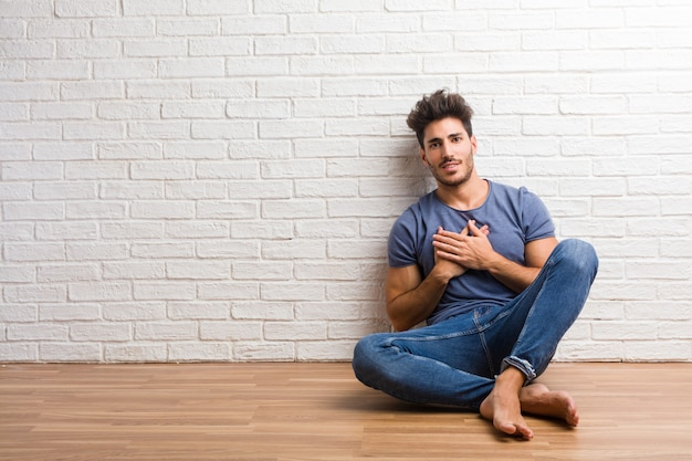 Young natural man sit on a wooden floor doing a romantic gesture