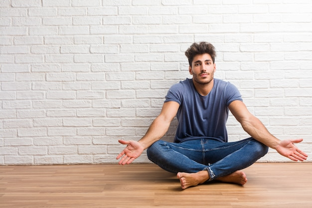 Young natural man sit on a wooden floor doubting and shrugging shoulders