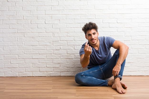 Young natural man sit on a wooden floor inviting to come, confident and smiling making a g