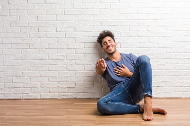 Young natural man sit on a wooden floor shouting, laughing and making fun of another, concept of mockery and uncontrol