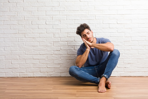 Young natural man sit on a wooden floor tired and very sleepy
