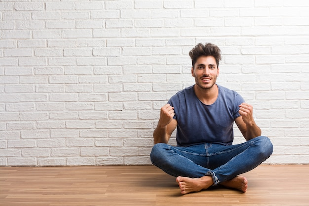 Young natural man sit on a wooden floor very happy and excited, raising arms, celebrating a victory or success, winning the lottery