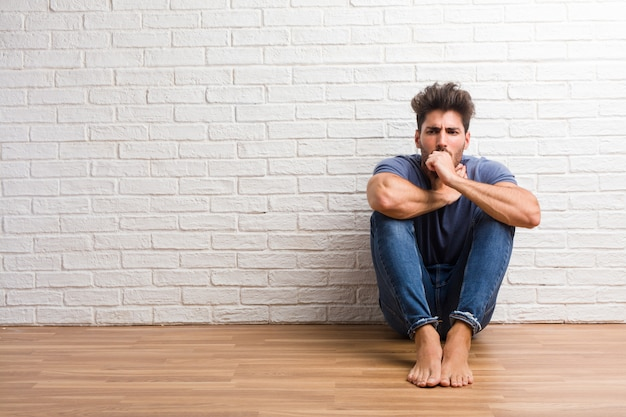 Young natural man sit on a wooden floor with a sore throat, sick due to a virus
