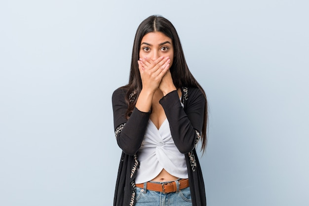 Young natural and pretty arab woman shocked covering mouth with hands.