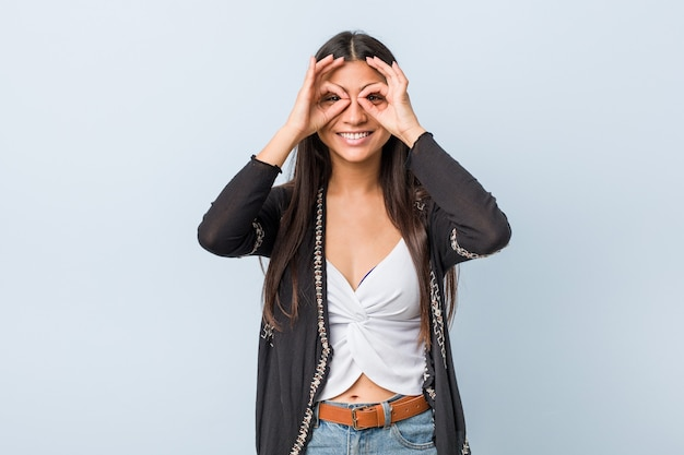 Young natural and pretty arab woman showing okay sign on eyes