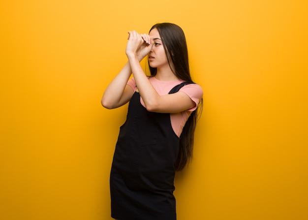 スパイグラスのジェスチャーを作る若い自然なかわいい女の子
