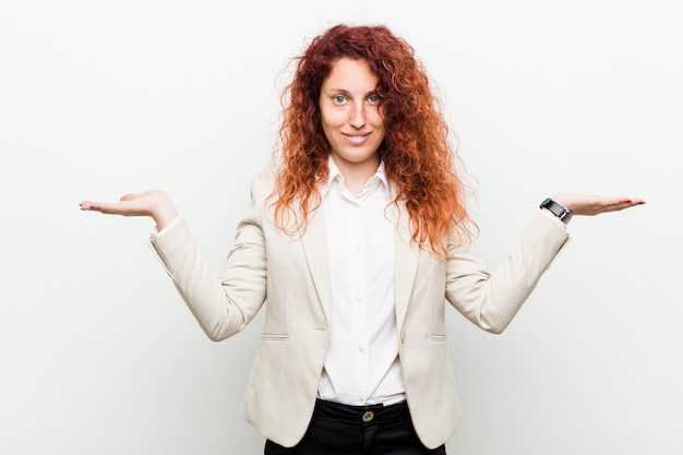 Young natural redhead business woman isolated against white background makes scale with arms