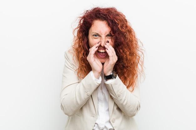正面に興奮して叫んで白い背景に対して孤立した若い自然赤毛のビジネス女性。