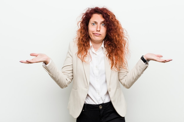 Young natural redhead business woman isolated against white wall doubting and shrugging shoulders in questioning gesture.