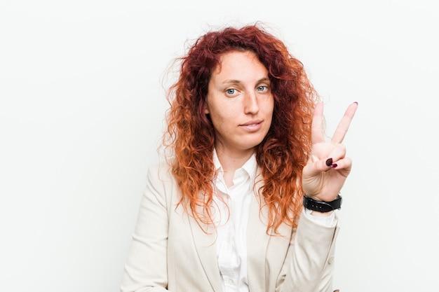 指で2番目を示す白い壁に対して隔離される若い自然な赤毛ビジネス女性。