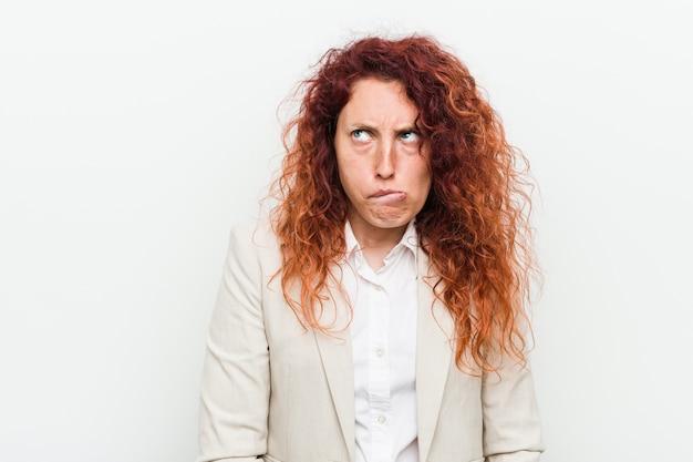 混乱している白で隔離される若い自然な赤毛のビジネス女性は疑わしく感じています。