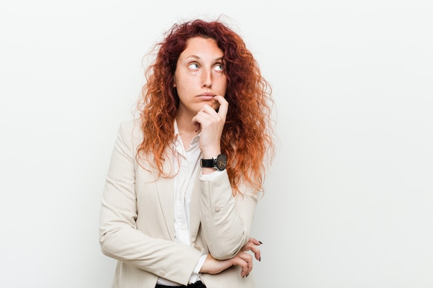Young natural redhead business woman looking sideways with doubtful and skeptical expression.