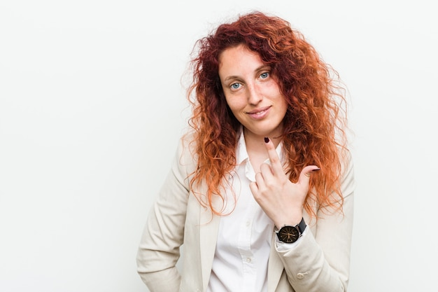 Young natural redhead business woman pointing with finger at you as if inviting come closer.