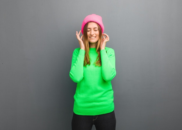 手で耳を覆う若い自然なロシアの女性