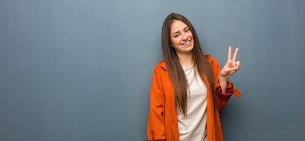 Молодая естественная женщина делает жест победы