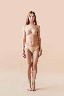 Молодая натуральная женщина позирует в нижнем белье