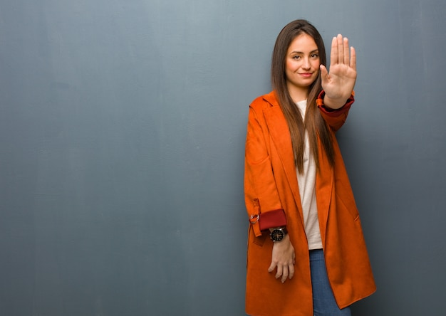 Young natural woman putting hand in front