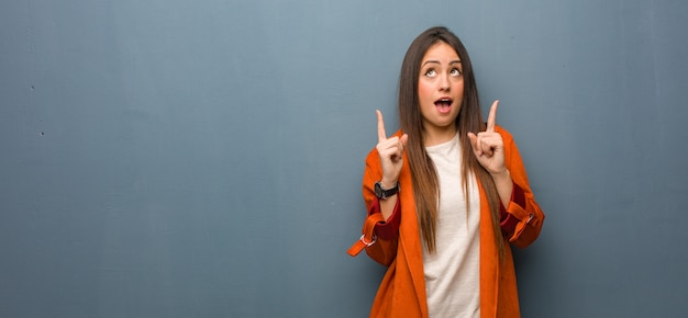 Young natural woman surprised pointing up to show something