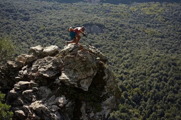 Молодой фотограф-натуралист на вершине горы