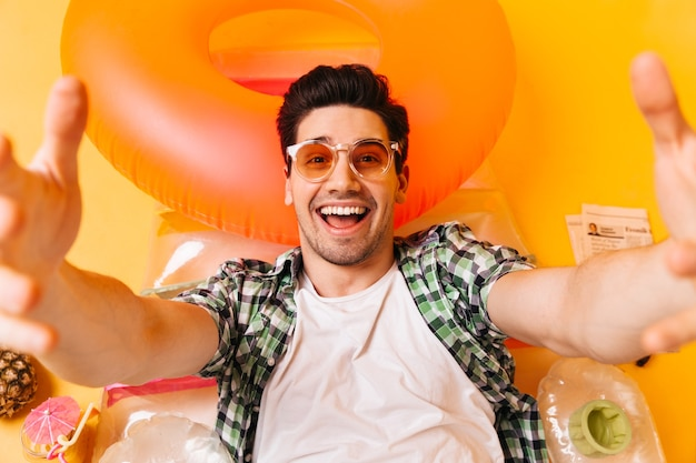 Young naughty man in plaid shirt and orange glasses smiles and takes selfie on inflatable mattress.