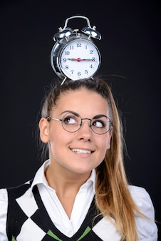 Young nerd woman holding an alarm clock on head.