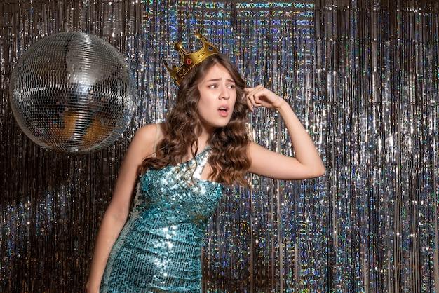 파티에서 왕관과 함께 장식 조각과 푸른 녹색 반짝이 드레스를 입고 젊은 긴장 아름다운 아가씨