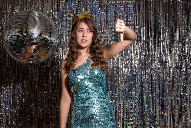 파티에서 아래를 가리키는 왕관과 함께 장식 조각으로 파란색 녹색 반짝이 드레스를 입고 젊은 긴장 아름다운 아가씨