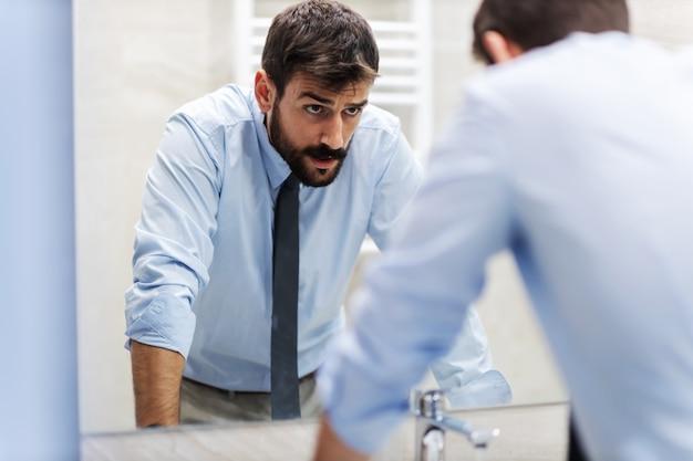シンクに寄りかかってトイレの鏡で自分自身を見ている若い神経質なビジネスマン。