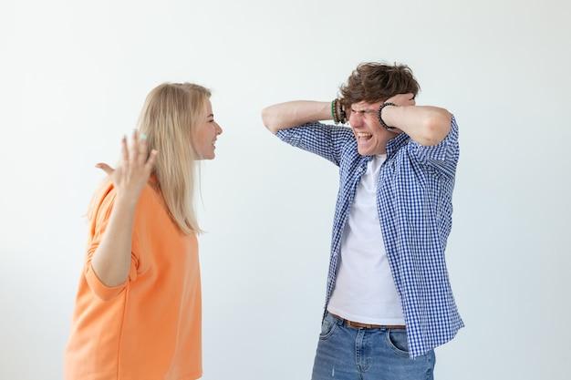 若い神経質なカップルはかわいい女の子を邪悪にし、耳を塞いでいる若い男を怒らせて立っている