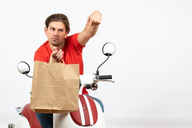흰 벽에 종이 가방을 가리키는 스쿠터에 앉아 빨간 제복을 입은 젊은 긴장 택배 남자