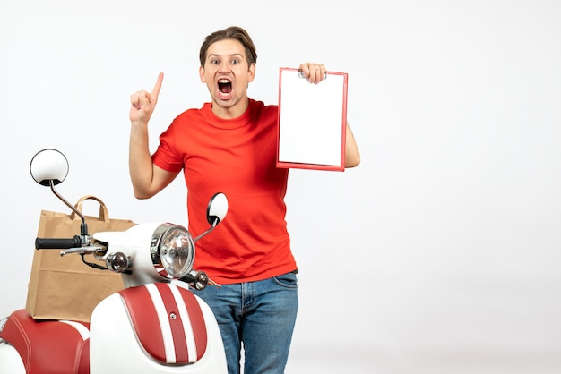 Young nervous and emotional delivery guy in red uniform standing near scooter showing document on white wall