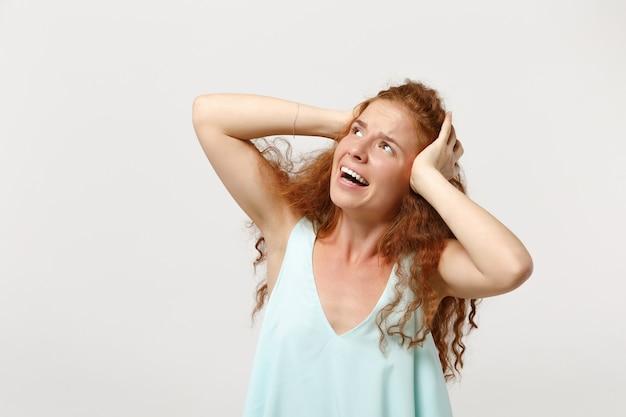 스튜디오에서 흰색 배경에 격리된 채 캐주얼한 가벼운 옷을 입은 젊은 긴장된 빨간 머리 여성. 사람들은 진심 어린 감정 라이프 스타일 개념입니다. 복사 공간을 비웃습니다. 올려다보고, 머리에 손을 얹습니다.