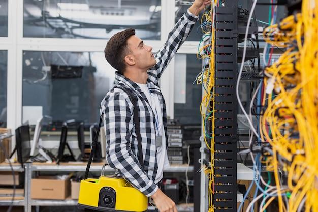 Молодой сетевой инженер с коробкой смотрит на коммутаторы ethernet