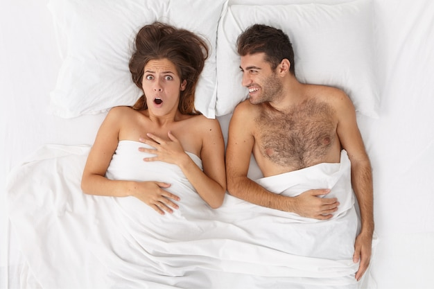 Young newlywed couple wake up in morning. frightened woman recalls something astonishing, cheerful husband lies near in comfortable bed under white sheet. people, home, relationship, bedding concept