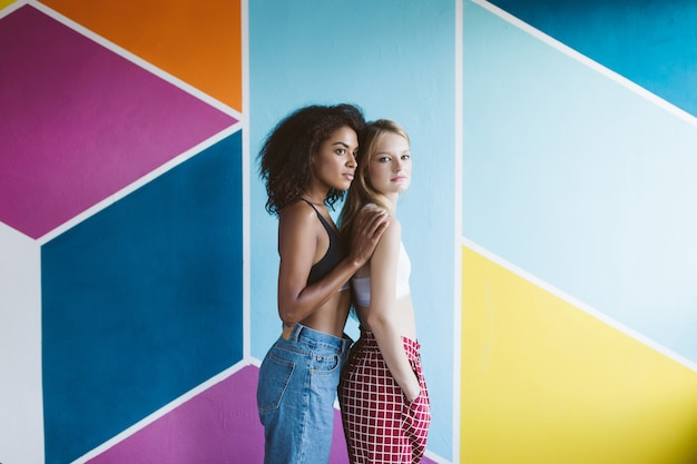 Young nice african american woman with dark curly hair and pretty woman with blond hair in sporty tops dreamily looking aside together with colorful wall  isolated
