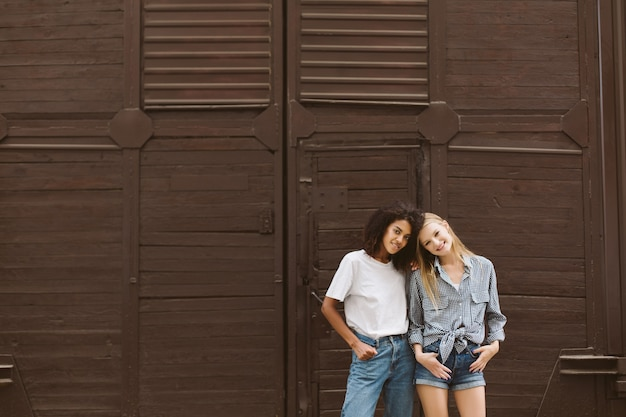 Young nice african american woman with dark curly hair in t-shirt and jeans and cute woman with blond hair in shirt and denim shorts joyfully  with brown wall