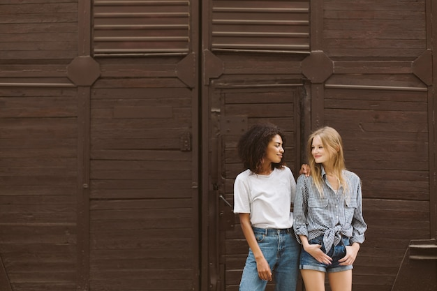Young nice african american woman with dark curly hair in t-shirt and jeans and pretty woman with blond hair in shirt and denim shorts happily looking at each other with brown wall